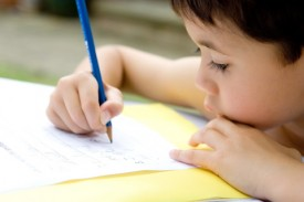 Young boy enjoying his handwriting homework, outdoors.